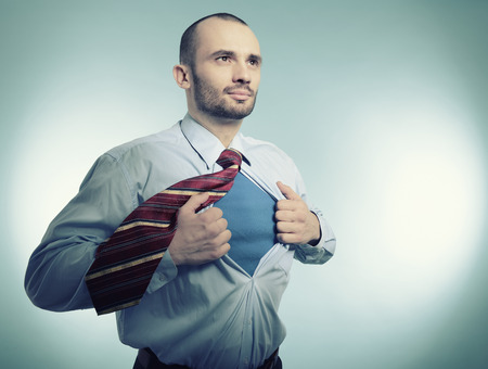 青い背景上ヒーロー ビジネス manopening、スーパー ヒーローのような彼のシャツを超します。 写真素材