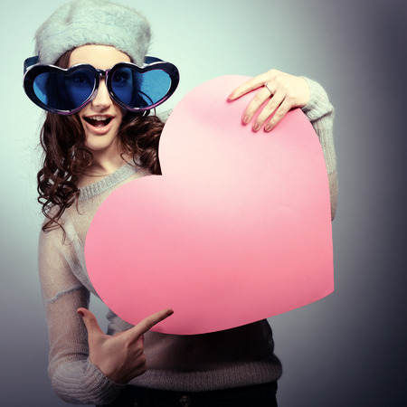 Cute attractive fashion young girl posing with funny big love gllasses and pointing at pink heart, toned photo