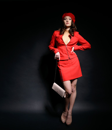 Stylish fashion girl in red  suit and beret with clutch posing at studio over black background