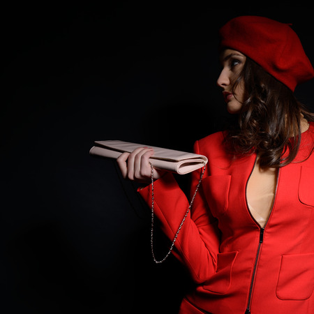 frenchwoman: Stylish fashion girl in red suit and beret with, posing at studio over black background