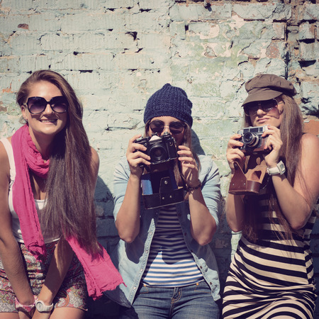 group shot: urban girls have fun with vintage photo cameras outdoor near grunge wall, image toned