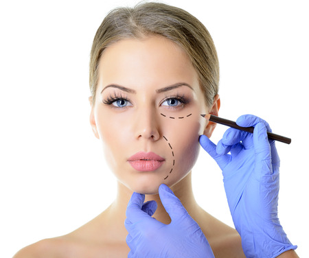 lift hands: Beautiful woman ready for cosmetic surgery, female face with doctors hands with pencil, over white Stock Photo