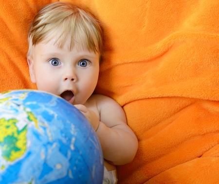 niños reciclando: Bebé feliz jugando con el globo terrestre en un plaid naranja