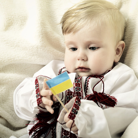 national costume: portrait of cute baby boy in national costume plaing with ucrainian flag, toned