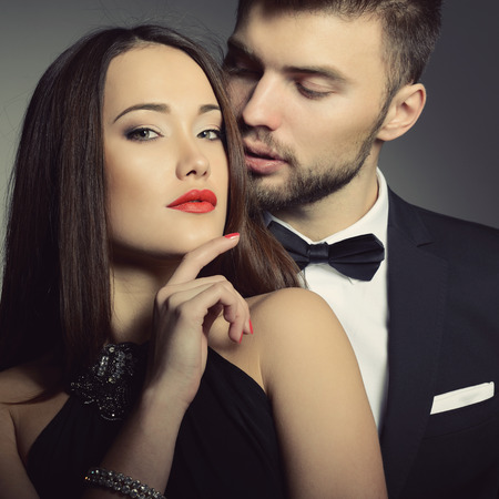 elegance: Sexy passion couple in love. Portrait of beautiful young man and woman dressed in classic clothes, studio shot over grey background