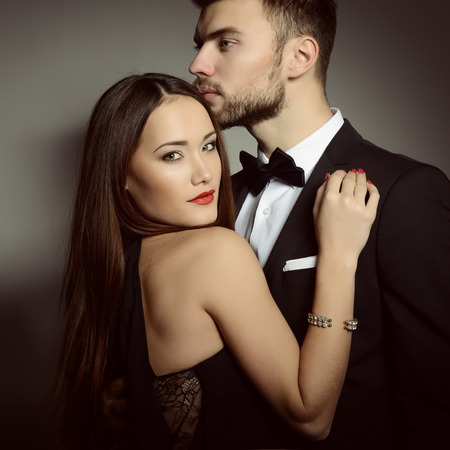 열정: 사랑 섹시 열정 커플. 고전적인 옷을 입고 아름다운 젊은 남자와 여자의 초상화, 스튜디오 회색 배경 위에 총을