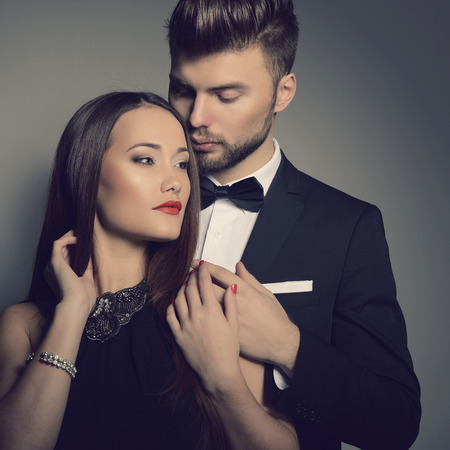 Sexy passion couple in love. Portrait of beautiful young man and woman dressed in classic clothes, studio shot over grey background  photo