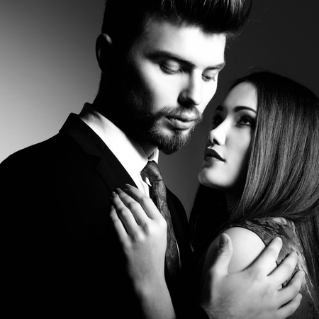 the passion: Portrait of beautiful young man and woman dressed in classic clothes, studio shot over grey background. Sexy passion couple in love.  Stock Photo