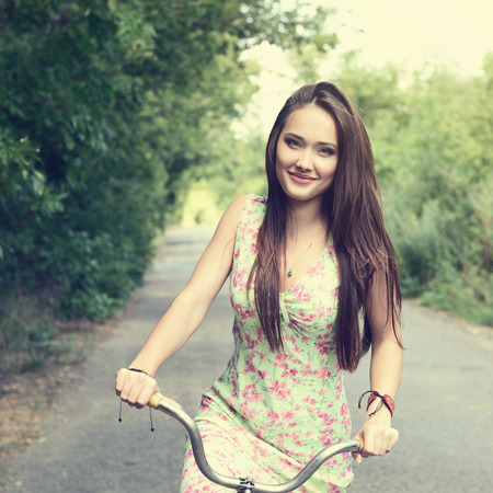 Happy young beautiful woman with retro bicycle. Portrait of fresh girl with cycle over summer outdoor, image toned. photo