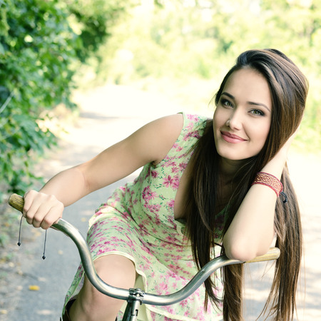 Happy young beautiful woman with retro bicycle. Portrait of fresh girl with cycle over summer outdoor, image toned.
