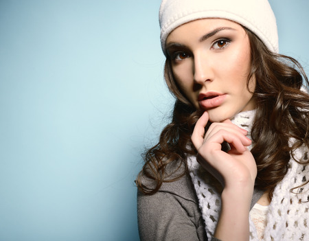 nat: Beautiful young woman posing at studio in white nat and scarf Stock Photo