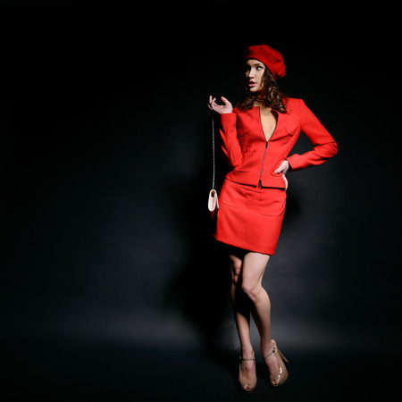frenchwoman: Stylish fashion girl in red  suit and beret with clutch looking left at copyspace, posing at studio over black background