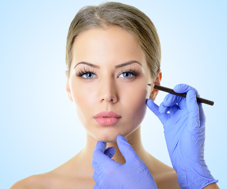 Beautiful woman ready for cosmetic surgery, female face with doctor's hands with pencil, over blue Stockfoto