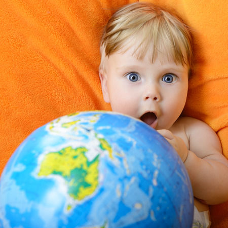 Happy baby playing with terrestrial globe on an orange plaid photo