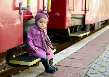 Little cute girl ready to vacation on railway station, baby girl fashion model go on travels photo