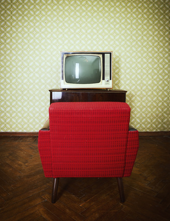 Vintage room with two old fashioned armchair and retro tvover obsolete wallpaper. Toned photo