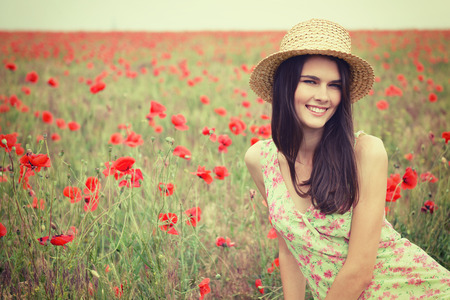 gentle dream vacation: Young beautiful calm girl in straw hat dreamomg on a poppy field, summer outdoor. Toned. Stock Photo