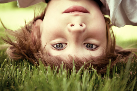 Happy little boy standing upside down on green grass in spring park, toned photo