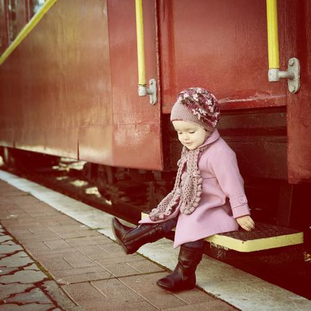 Niña linda lista para las vacaciones en la estación de tren, modelo de la manera del bebé ir en viajes, tonos