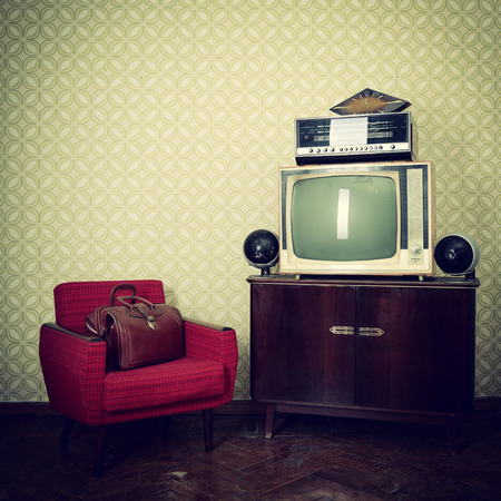 old fashioned tv: Vintage room with wallpaper, old fashioned armchair, retro tv, bag, clocks, radio player and loudspeakers Stock Photo