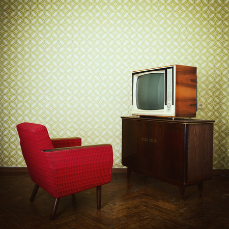 60s fashion: Vintage room with two old fashioned armchair and retro tvover obsolete wallpaper. Toned