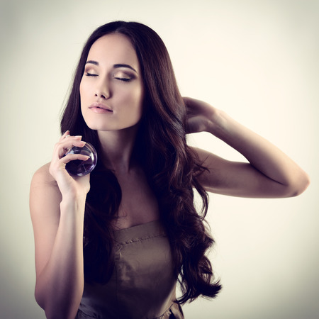 Girl with perfume, young beautiful woman holding bottle of perfume and smelling aroma, toned soft beige and noise added  photo