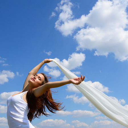 Happy young woman holding white scarf with opened arms expressing freedom, outdoor shot against blue sky. photo