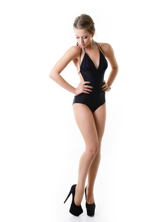 Sexy young woman posing in a black swimsuit full length isolated studio portrait, over white background photo