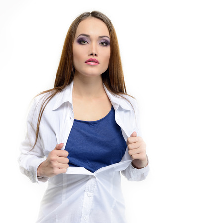 Young pretty woman opening her shirt like a superhero. Super girl over white.  Stock Photo
