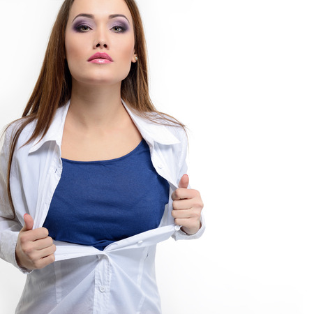 ripping shirt: Young pretty woman opening her shirt like a superhero. Super girl over white.  Stock Photo