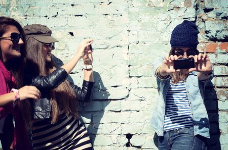 fin de semana: Muchachas que se divierten juntos al aire libre y hacer fotos con el teléfono elegante, estilo de vida, tonificada y ruido añadido