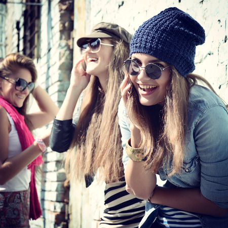 Girls having fun together outdoors and calling smart phone, lifestyle. Instagram effect. 스톡 콘텐츠