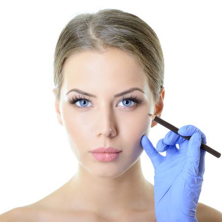 Bella donna pronta per la chirurgia estetica, volto femminile con le mani del medico con la matita, su bianco
