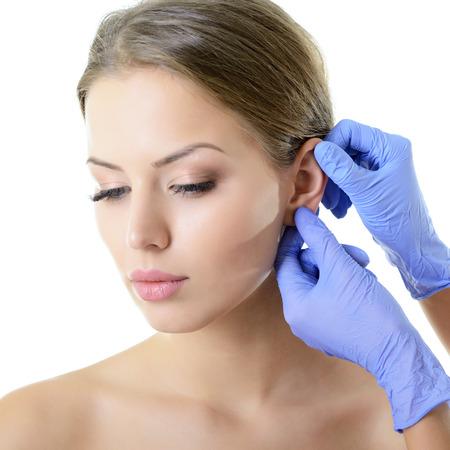 Gesicht der jungen Frau mit Schönheitsbehandlung Ohr Kunststoff isoliert