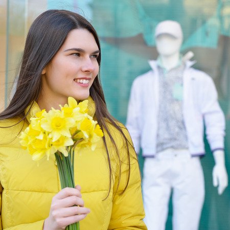 shopwindow: Portrait of young beautiful woman with sping flowers, outdoor over shopwindow with dummy. Stock Photo
