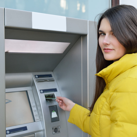 withdrawing: Young woman withdrawing money from credit card at ATM