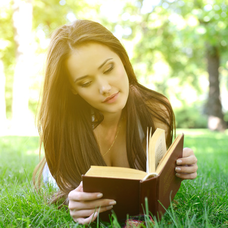 Beautiful girl reading book in the summer park, image toned. Stockfoto
