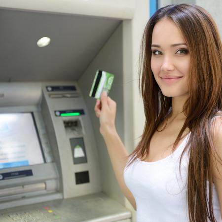 若い女性の ATM でのクレジット カードからお金を引き出す