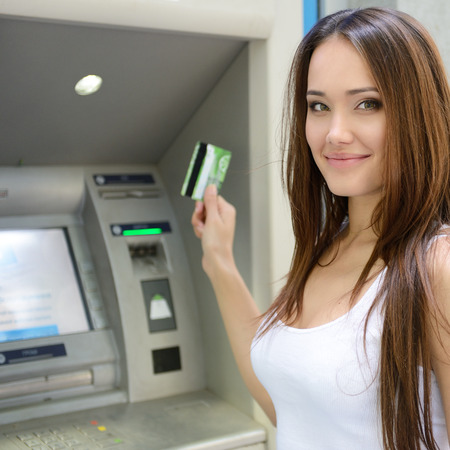 deposit slip: Young woman withdrawing money from credit card at ATM