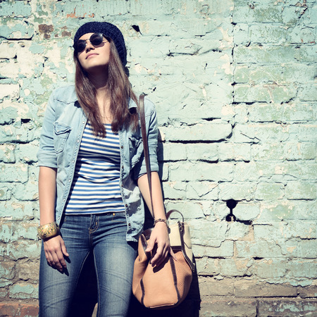 beautiful cool girl in hat and sunglasses against grunge wall, toned photo