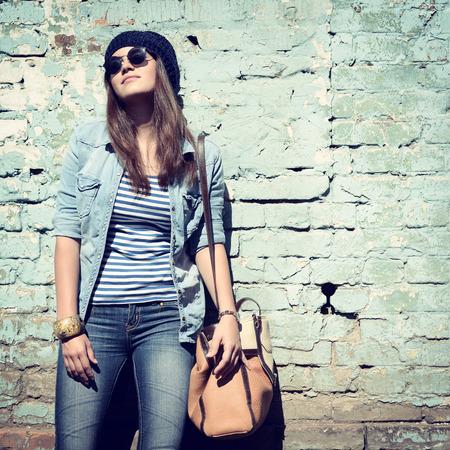 szép hűvös lány kalapban és napszemüvegben ellen, grunge fal, tónusú Stock fotó