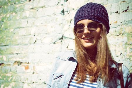 Schöne coole Mädchen in Hut und Sonnenbrille gegen Grunge Wand, getönten Standard-Bild - 29092721