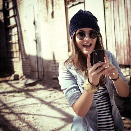 Pretty young woman using mobile phone and getting photos, outdoor. Toned. photo
