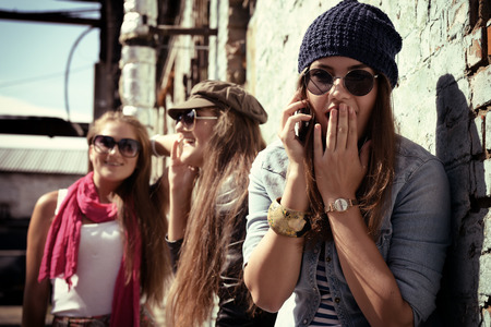 Girls having fun together outdoors and calling smart phone, lifestyle. Instagram effect. Banque d'images