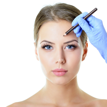 face lift: Beautiful woman ready for cosmetic surgery, female face with doctors hands with pencil, over white Stock Photo
