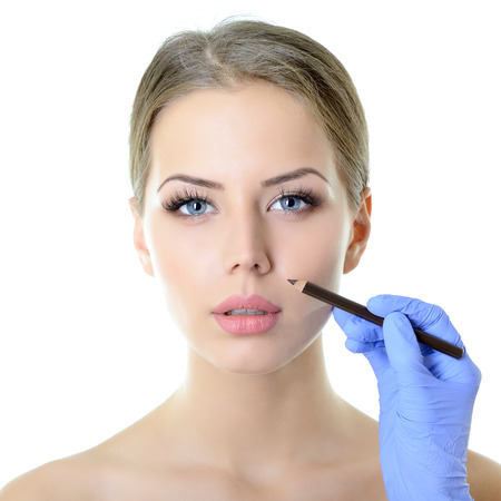 Beautiful woman ready for cosmetic surgery, female face with doctors hands with pencil, over white photo