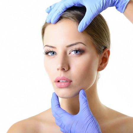 若い美しい女性顔、白で隔離の美しい若い女性の手袋タッチ顔で医師の手の美容トリートメント