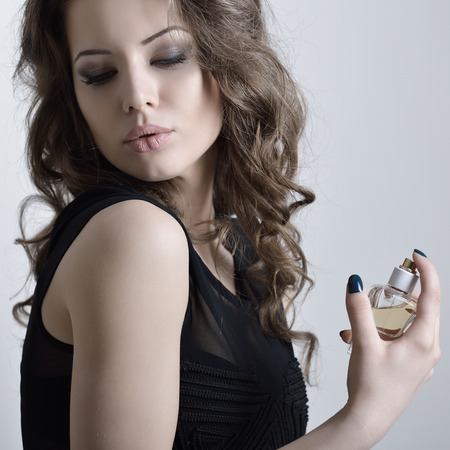 Girl with perfume, young beautiful woman holding bottle of perfume and smelling aroma, toned. photo