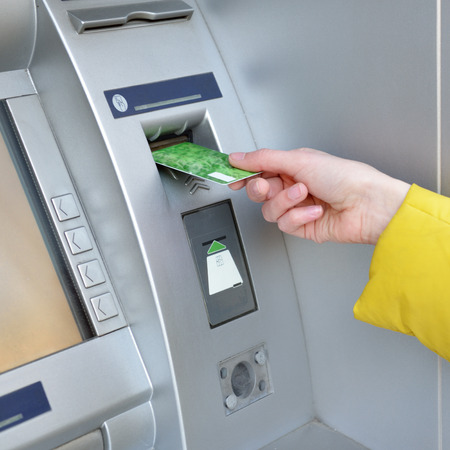 Woman withdrawing money from credit card at ATM, hand closep. Stock Photo