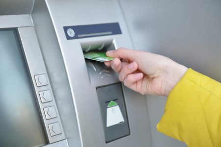 Woman withdrawing money from credit card at ATM, hand closep. 스톡 콘텐츠